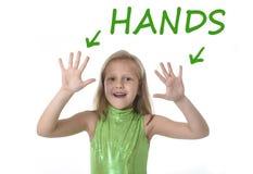 显示手的逗人喜爱的小女孩在学会英国词的身体局部在学校 免版税库存图片