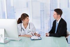 显示报告的医生对商人在诊所 库存图片