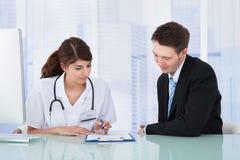 显示报告的医生对商人在诊所 免版税库存照片