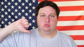 显示拇指下来在美国旗子的背景的大人 显示反感标志用手的人 股票录像