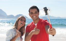 显示拇指和采取与电话的拉丁夫妇selfie 免版税库存照片