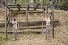 显示拇指的军事战士,当拿着绳索在新兵训练所训练期间时 免版税库存图片
