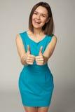 显示拇指的愉快的微笑的美丽的少妇 免版税库存图片