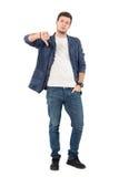 显示拇指的牛仔裤的失望的年轻人下来打手势在照相机 图库摄影