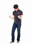 显示拳头和愉快的标志的年轻亚裔人。 库存照片