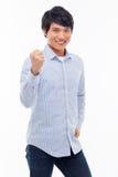 显示拳头和愉快的标志的年轻亚裔人。 免版税库存照片
