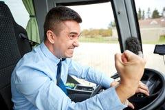 显示拳头和驾驶公共汽车的恼怒的司机 免版税库存照片