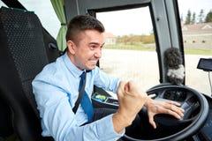 显示拳头和驾驶公共汽车的恼怒的司机 免版税库存图片