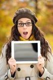 显示数字式片剂屏幕的惊奇的妇女在秋天 库存照片