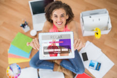 显示数字式片剂的微笑的女实业家的综合图象在创造性的办公室 免版税图库摄影