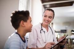 显示数字式片剂的微笑的女性治疗师对男孩 库存图片