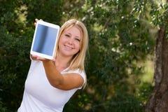 显示数字式片剂的白肤金发的少年在照相机 免版税库存图片