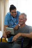 显示数字式片剂的老人对医生在养老院 免版税库存照片