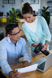 显示数字照相机的女实业家对同事 免版税库存图片