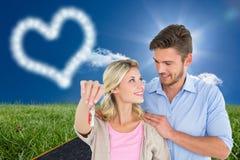 显示新房钥匙的有吸引力的年轻夫妇的综合图象 免版税库存照片