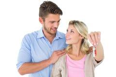 显示新房钥匙的有吸引力的年轻夫妇 免版税库存照片