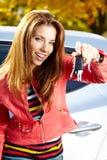 显示新的汽车钥匙和汽车的汽车司机妇女。 免版税库存图片