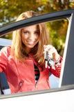 显示新的汽车钥匙和汽车的汽车司机妇女。 免版税库存照片
