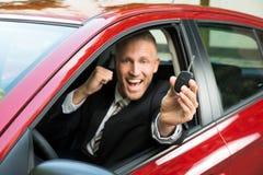 显示新的汽车钥匙的激动的商人 库存照片