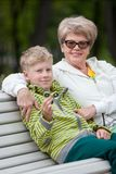 显示新的锭床工人小配件,愉快的资深祖母的年轻孙子拥抱长凳的男孩在公园天 免版税库存图片