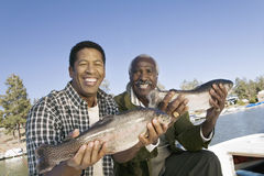 显示新近地被抓的鱼的父亲和儿子 库存照片