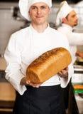 显示新近地被烘烤的整个五谷面包的厨师 免版税库存照片