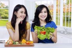 显示新鲜的沙拉的两个快乐的女孩 免版税图库摄影