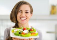显示新鲜的沙拉的微笑的少妇 免版税图库摄影