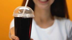 显示新鲜的碳酸化合的饮料的手套的微笑的女孩入照相机,关闭  股票录像