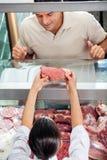 显示新鲜的红肉的屠户对顾客 库存图片