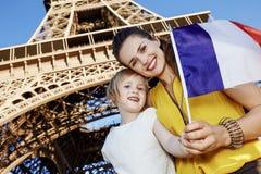 显示旗子的母亲和儿童游人在埃佛尔铁塔,巴黎附近 免版税库存照片