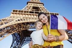 显示旗子的母亲和儿童游人在埃佛尔铁塔,巴黎附近 库存照片