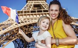 显示旗子的母亲和女儿旅行家反对埃佛尔铁塔 图库摄影