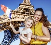 显示旗子的母亲和女儿旅行家反对埃佛尔铁塔 库存图片