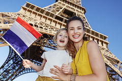 显示旗子的母亲和女儿旅行家在埃佛尔铁塔附近 免版税库存图片