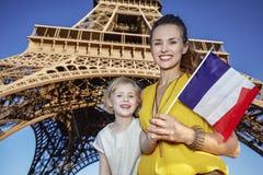 显示旗子的母亲和女儿游人反对埃佛尔铁塔 库存图片