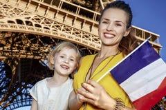 显示旗子的母亲和女儿游人反对埃佛尔铁塔 免版税库存图片