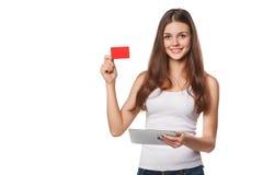 显示无具体金额的信用证卡片的微笑的妇女拿着片剂个人计算机手中,在白色T恤杉,被隔绝在灰色背景 免版税图库摄影