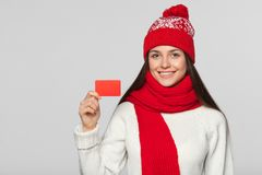 显示无具体金额的信用证卡片,冬天概念的微笑的妇女 红色拿着卡片的帽子和围巾的愉快的女孩,被隔绝在灰色 免版税库存照片