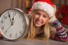 显示时钟的圣诞老人帽子的微笑的十几岁的女孩 免版税库存照片