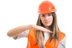 显示时间的美丽的年轻女性建筑师打手势 免版税图库摄影