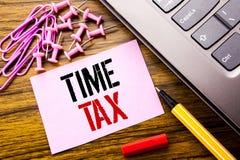 显示时间税的手写的文本 征税在木的桃红色稠粘的便条纸写的财务提示的企业概念 库存照片