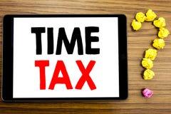显示时间税的文字文本 征税在木背景的片剂计算机写的财务提示的企业概念 库存图片