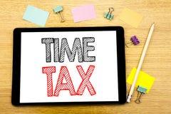 显示时间税的文字文本 征税在片剂膝上型计算机写的财务提示的企业概念,与sti的木背景 库存照片