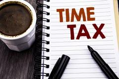 显示时间税的文字文本 征税在笔记本在木wo的笔访纸写的财务提示的企业概念 库存图片