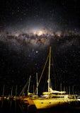 显示星和银河与小船的夜空在前景 免版税库存图片