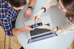 显示智能手机的屏幕男人和妇女坐在桌上 库存照片