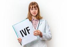 显示有书面文本的女性医生剪贴板:IVF 库存照片
