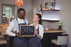 显示有开放标志的微笑的侍者和女服务员黑板在柜台 库存照片