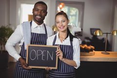 显示有开放标志的微笑的侍者和女服务员黑板 免版税库存图片